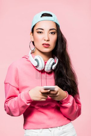 skeptical asian woman in pullover and cap with headphones holding smartphone isolated on pink