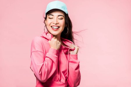 Photo pour Attractive asian woman with closed eyes in pink pullover and cap smiling isolated on pink - image libre de droit