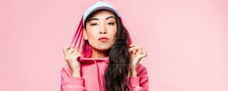 Photo pour Panoramic shot of attractive asian woman in pink pullover and cap looking at camera isolated on pink - image libre de droit