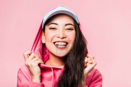 Photo for Attractive asian woman in pink pullover and cap smiling isolated on pink - Royalty Free Image