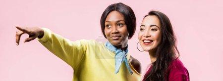 Photo pour Photo panoramique d'amis américains asiatiques et africains souriants pointant du doigt isolés sur le rose - image libre de droit