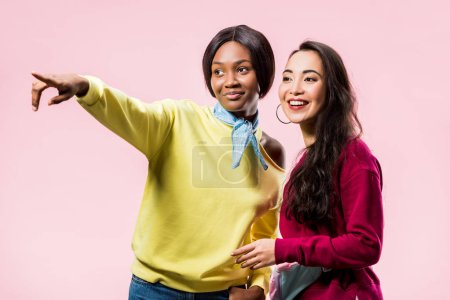 Photo pour Souriant asiatique et afro-américain amis pointant avec doigt isolé sur rose - image libre de droit