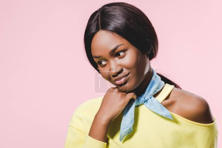 Photo for Pensive african american woman in yellow pullover and scarf looking down isolated on pink - Royalty Free Image