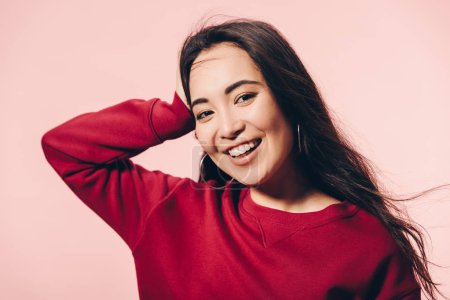 Photo pour Attractive asian woman in red sweater smiling isolated on pink - image libre de droit