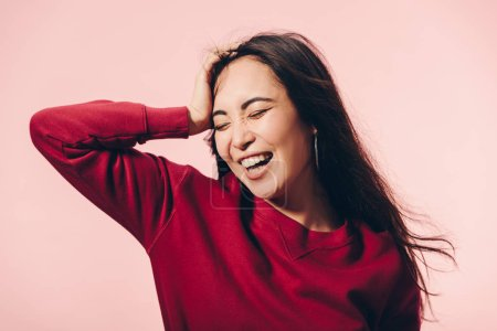 Photo pour Attractive asian woman in red sweater with closed eyes smiling isolated on pink - image libre de droit