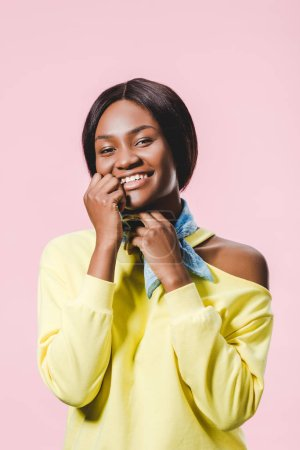 Photo for Smiling african american woman in yellow pullover and scarf looking at camera isolated on pink - Royalty Free Image