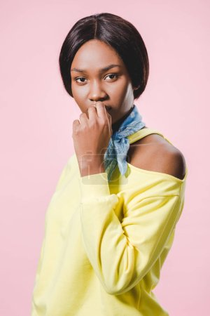 Photo for Pensive african american woman in yellow pullover and scarf looking at camera isolated on pink - Royalty Free Image