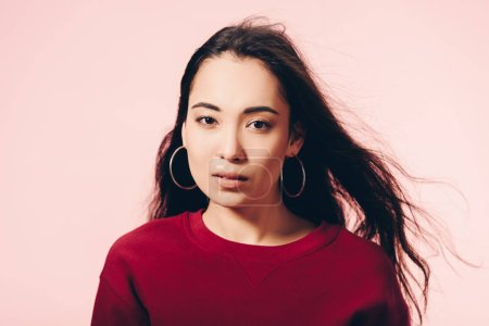 Photo pour Attractive asian woman in red sweater looking at camera isolated on pink - image libre de droit