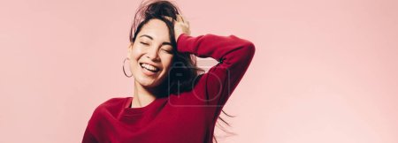 Photo for Panoramic shot of attractive asian woman in red sweater smiling isolated on pink - Royalty Free Image