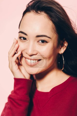 Photo for Attractive asian woman in red sweater smiling isolated on pink - Royalty Free Image
