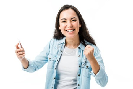 Photo for Attractive asian woman in denim shirt showing yes gesture and holding smartphone isolated on white - Royalty Free Image