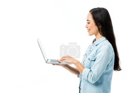Photo pour Side view of attractive asian woman in denim shirt smiling and holding laptop isolated on white - image libre de droit
