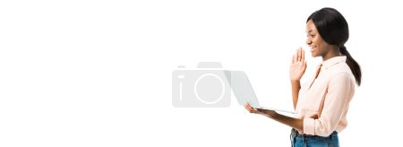 Photo for Panoramic shot of african american woman in shirt holding laptop and talking in video chat isolated on white - Royalty Free Image