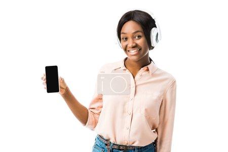 Foto de Sonriente mujer afriamericana vestida de camisa con auriculares que sostienen teléfonos inteligentes aislados sobre blanco. - Imagen libre de derechos