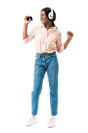 Photo pour Une Africaine américaine souriante en chemise avec des écouteurs tenant un smartphone et dansant isolée sur blanc - image libre de droit
