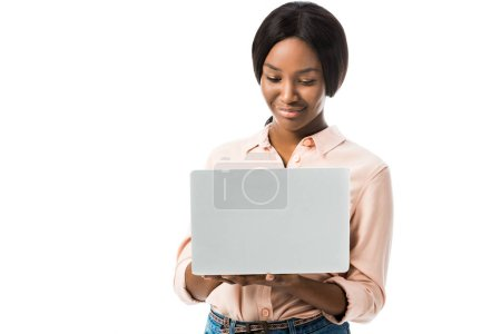 Foto de Sonriente mujer afriamericana vestida con un portátil aislado en blanco. - Imagen libre de derechos