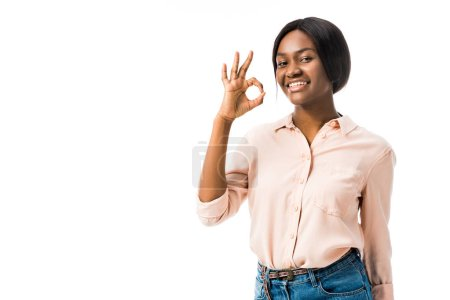 smiling african american woman showing ok gesture isolated on white
