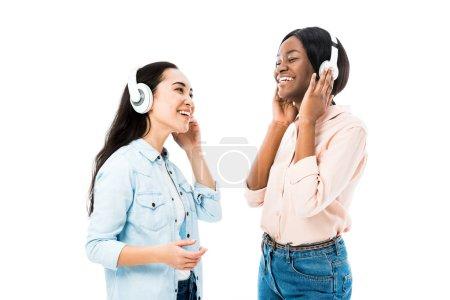 Foto de Smiling asian and african american friends listening music in headphones isolated on white - Imagen libre de derechos