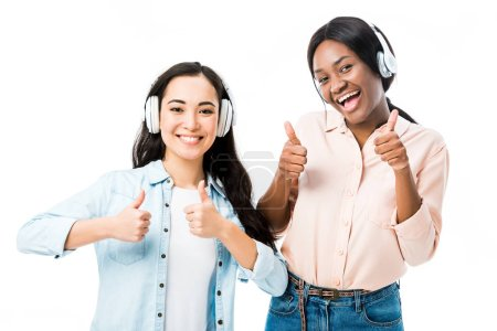 Photo for Smiling asian and african american friends in headphones showing thumbs up isolated on white - Royalty Free Image