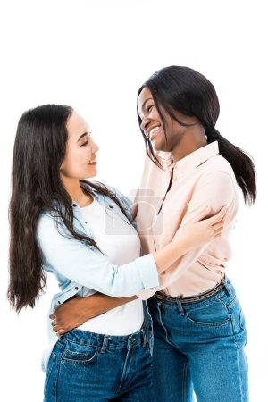 Foto de Sonriente asiático y africano americano amigos abrazo aislado en blanco - Imagen libre de derechos