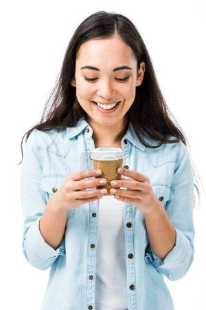 Photo pour Attrayant et souriant asiatique femme en denim chemise tenant tasse en papier isolé sur blanc - image libre de droit