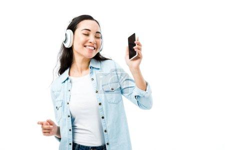 Photo pour Attrayant et souriant asiatique femme en denim chemise écouter de la musique et tenant smartphone isolé sur blanc - image libre de droit