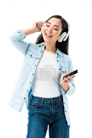 Photo for Attractive and smiling asian woman in denim shirt listening music and holding smartphone isolated on white - Royalty Free Image