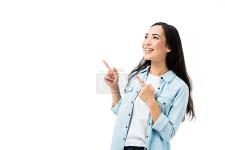 Photo for Attractive and smiling asian woman in denim shirt pointing with fingers isolated on white - Royalty Free Image