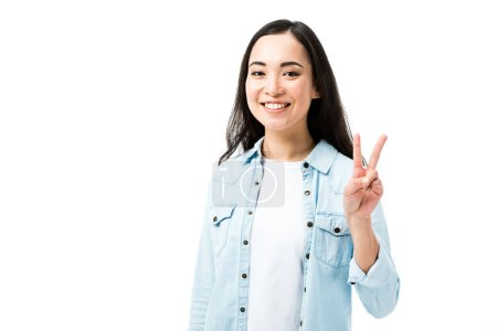 Photo pour Séduisante et souriante femme asiatique en chemise en denim montrant le signe de la paix isolée sur blanc - image libre de droit