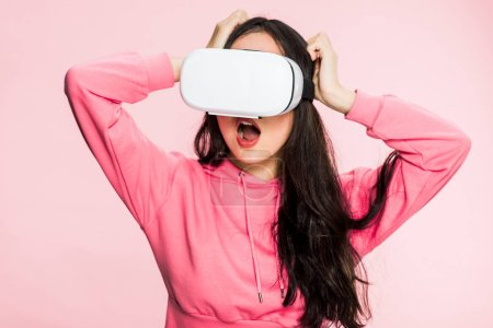 Photo for Shocked woman in pink pullover with virtual reality headset isolated on pink - Royalty Free Image