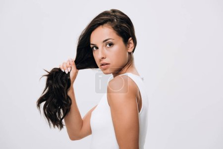 Photo for Brunette beautiful woman holding long healthy and shiny hair isolated on grey - Royalty Free Image