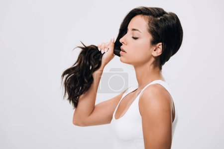 Photo for Side view of brunette beautiful woman holding long healthy and shiny hair isolated on grey - Royalty Free Image