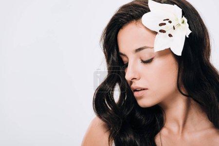 Foto de Morena hermosa mujer con los ojos cerrados y lirio en el pelo largo y saludable aislado en gris - Imagen libre de derechos