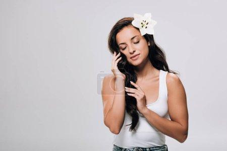 Foto de Tierna morena hermosa mujer con los ojos cerrados y lirio en el pelo largo y saludable aislado en gris - Imagen libre de derechos
