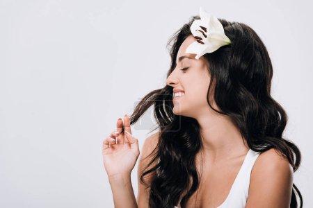 Photo pour Belle femme de brunette de sourire avec le lys dans le long cheveu sain d'isolement sur le gris - image libre de droit