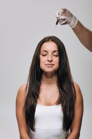 Photo pour Cosmétologue dans des gants de latex faisant la mésothérapie de cuir chevelu à la belle femme brune avec le long cheveu isolé sur le gris - image libre de droit