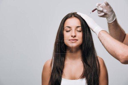 Photo pour Cosmétologue dans les gants de latex faisant la mésothérapie de cuir chevelu à la belle femme brune avec les cheveux longs et les yeux fermés isolés sur le gris - image libre de droit