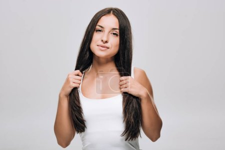 Photo for Brunette beautiful woman holding long straight healthy and shiny hair isolated on grey - Royalty Free Image