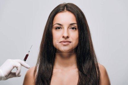 Photo pour Cosmétologue dans les gants de latex retenant la seringue pour la mésothérapie de cuir chevelu près de la belle femme de brunette avec le long cheveu isolé sur le gris - image libre de droit