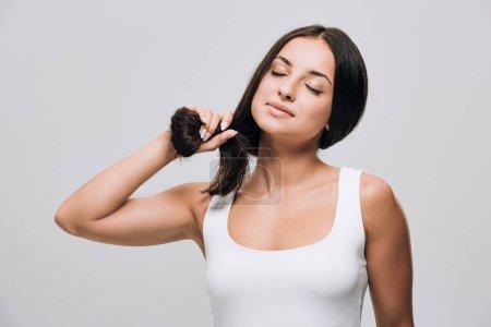 Photo pour Belle femme brune avec les yeux fermés retenant le long cheveu sain et brillant droit d'isolement sur le gris - image libre de droit