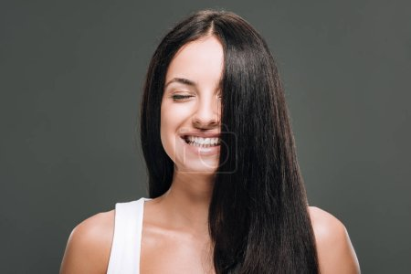 happy brunette beautiful woman with long straight healthy and shiny hair isolated on grey