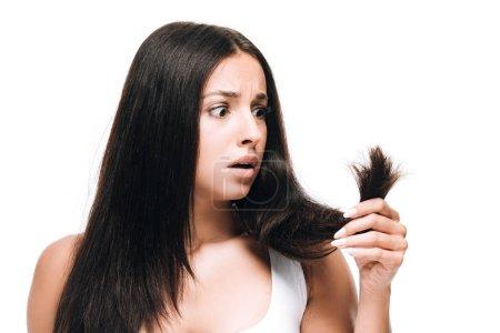 Photo pour Femme belle de brunette effrayée regardant le long cheveu droit endommagé d'isolement sur le blanc - image libre de droit