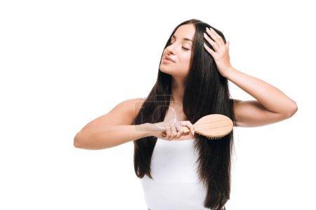 Photo pour Brunette belle femme aux yeux fermés brossant longs cheveux droits sains et brillants avec peigne isolé sur blanc - image libre de droit