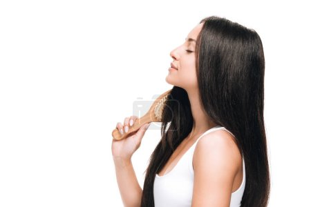 Photo for Side view of brunette beautiful woman with closed eyes brushing long straight healthy and shiny hair with comb isolated on white - Royalty Free Image