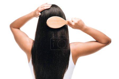 Photo pour Vue arrière de brune belle femme brossant longs cheveux droits sains et brillants avec peigne isolé sur blanc - image libre de droit