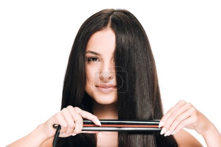 Photo for Brunette beautiful woman straightening long shiny hair with flat iron isolated on white - Royalty Free Image