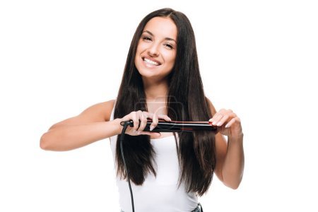 Photo for Smiling brunette beautiful woman straightening long shiny hair with flat iron isolated on white - Royalty Free Image