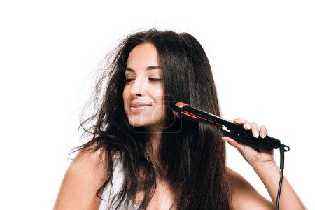 Foto de Sonriendo morena hermosa mujer estilismo cabello recto y rizado con hierro plano aislado en blanco - Imagen libre de derechos