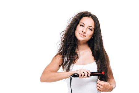 Photo pour Belle femme de brunette de sourire coiffant droit et bouclé s'est ressédu avec le fer plat d'isolement sur le blanc - image libre de droit