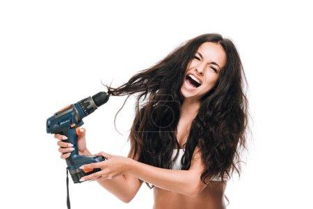 Photo pour Brunette belle femme à l'aide de marteau perceuse sur les cheveux et en criant isolé sur blanc - image libre de droit